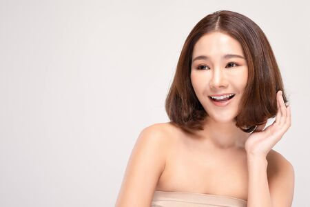Beautiful Young Asian Woman with short hair Looking While feeling so happy and cheerful with healthy Clean and Fresh skin,isolated on gray background,Beauty Cosmetics Concept 스톡 콘텐츠