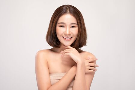 Beautiful Young Asian Woman with short hair Looking While Touching Chin feeling so happy and cheerful with healthy Clean and Fresh skin,isolated on gray background,Beauty Cosmetics Concept