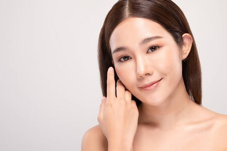 Beautiful Asian young woman touching soft cheek smile with clean and fresh skin Happiness and cheerful with positive emotional,isolated on white background,Beauty and Cosmetics Concept