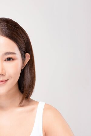 half of Beautiful Asian woman looking at camera smile with clean and fresh skin Happiness and cheerful with positive emotional,isolated on gray background,Beauty and Cosmetics Concept Фото со стока
