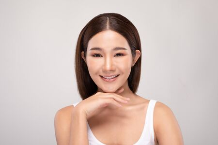 Beautiful Young Asian Woman Looking While Touching Chin feeling so happy and cheerful with healthy Clean and Fresh skin,isolated on white background,Beauty Cosmetics Concept Фото со стока