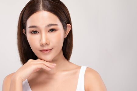 Beautiful Young Asian Woman Looking While Touching Chin feeling so happy and cheerful with healthy Clean and Fresh skin,isolated on white background,Beauty Cosmetics Concept Stock Photo
