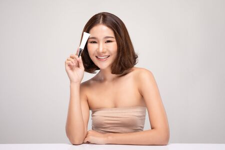 Beautiful Young Asian Woman with short hair Holding luxury white clean tube smile feeling so happy and cheerful with healthy Clean and Fresh skin,isolated on gray background,Beauty Cosmetics Concept