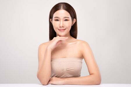 Beautiful Young Asian Woman Looking While Touching Chin feeling so happy and cheerful with healthy Clean and Fresh skin,isolated on gray background,Beauty Cosmetics Concept Stock Photo