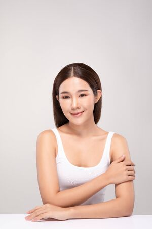 Beautiful Young Asian Woman Looking While Touching Shoulder feeling so happy and cheerful with healthy Clean and Fresh skin,isolated on gray background,Beauty Cosmetology Concept Stock Photo