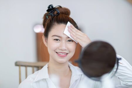 Portrait of a Beauty young woman brunette cosmetics looking in the mirror using tissue with toner for cleaning make up with fresh healthy facial skin,feeling so fresh and happiness,Beauty and Cosmetic Standard-Bild