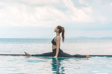 Asian young woman practice Yoga Monkey God Pose or Yoga Hanumanasana pose on the pool above the beach in the morning with beautiful sea in Tropical island,Feeling comfortable and relax in holiday