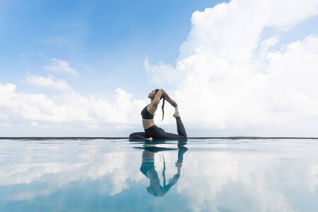 Vacation of Attractive Asian woman relaxing in yoga king pigeon pose on the pool above the beach with beautiful sea in Tropical island,Feeling comfortable and relax in holiday,Vacations Concept