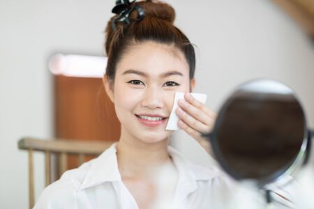 Portrait of a Beauty young woman brunette cosmetics looking in the mirror using tissue with toner for cleaning make up with fresh healthy facial skin,feeling so fresh and happiness,Beauty and Cosmetic 版權商用圖片