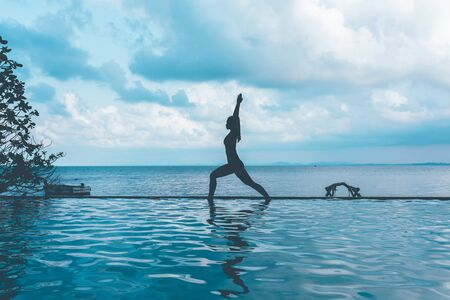 silhouette woman practice yoga Warrior one pose to meditation summer vacation on the pool above the beach,Travel in tropical beach Thailand,vacations and relaxation Concept