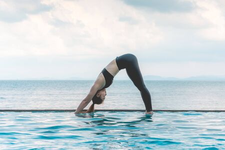woman practice yoga Downward Facing dog or yoga Adho Mukha Svanasana pose meditation summer vacation on the pool,Travel in tropical beach Thailand,vacations and relaxation Concept Stok Fotoğraf