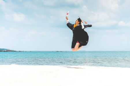 Graduated woman in cap and gown holding certificated jump celebrating in Commencement day with blue sky on the beach with beautiful sea in summer so proud happiness,Education Success in summer Concept