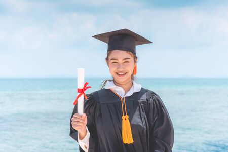 Graduated woman in cap and gown holding certificated celebrating in Commencement day with blue sky on the beach with beautiful sea in summer so proud and happiness,Education Success in summer Concept