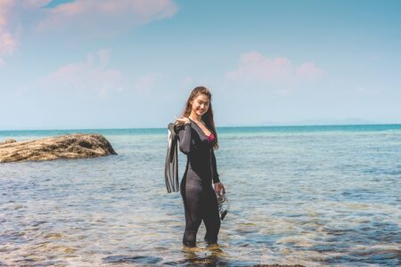 Vacations of Attractive Asian woman wearing wetsuit and holding Diving equipment fins and mask standing on seashore smile feeling so happiness and relax ready to dive,recreational diving Concept