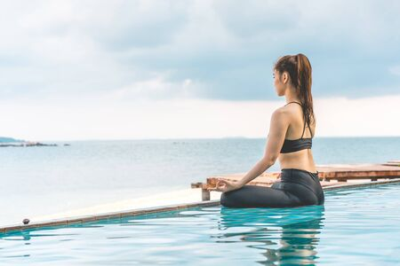 Vacation of Beautiful Attractive Asian woman relaxing in yoga lotus pose on the pool above the beach with beautiful sea in Tropical island,Feeling comfortable and relax in holiday,Vacations Concept