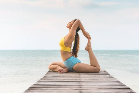 Vacation of Attractive Asian woman relaxing in yoga king pigeon pose on the pier above the beach with beautiful sea in Tropical island,Feeling comfortable and relax in holiday,Vacations Concept