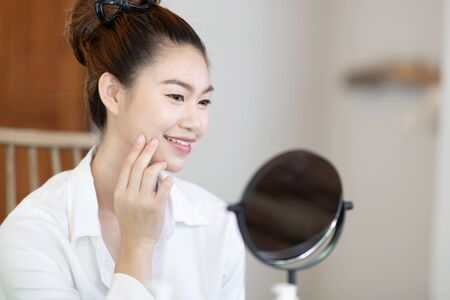 Portrait of a Beauty young woman brunette cosmetics looking in the mirror with fresh healthy facial skin,feeling so fresh and happiness,Beauty and Cosmetics Concept