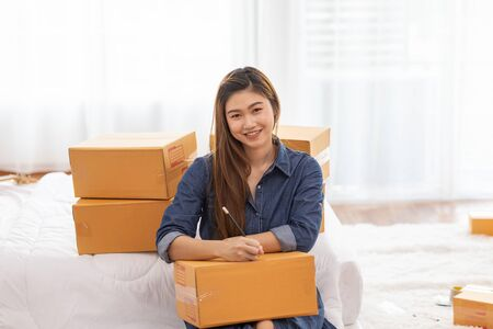 SME entrepreneur of Young women working with laptop and writing customer address for send order Online shopping at home,Cheerful and Happy with box for packaging in home,Startup and Freelance Concept Stock Photo