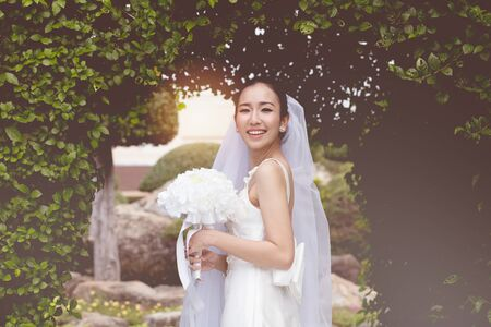 Beautiful Attractive Asian Bride Woman wearing white wedding dress and holding bouquet smile so proud and happiness in wedding day,Bride Concept Stock Photo