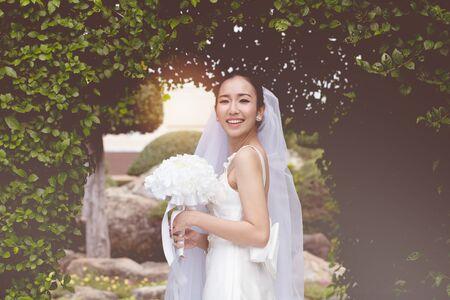 Schöne attraktive asiatische Brautfrau, die ein weißes Hochzeitskleid trägt und einen Blumenstrauß hält, so stolz und glücklich am Hochzeitstag, Brautkonzept Standard-Bild