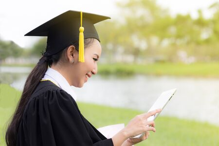 Graduate playing tablet in her hand feeling relaxing and so happiness in Commencement day 写真素材