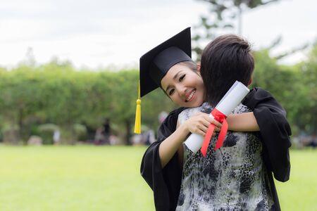 Schöne attraktive asiatische Absolventin in Mütze und Kleid, die die Umarmung mit den Eltern feiert, die am Anfangstag so stolz und glücklich sind, Erfolgskonzept für die Abschlussausbildung