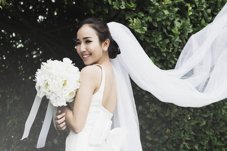 Beautiful Attractive Asian bride wearing wedding dress smile and holding bouquet,Feeling so proud and happiness in wedding day,Vintage Tone