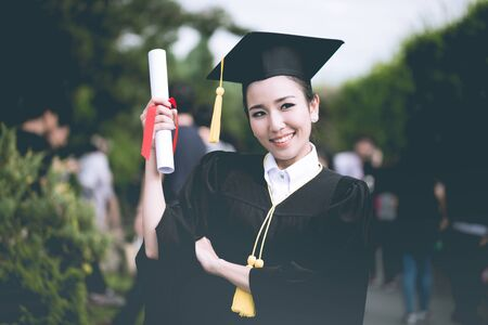 Attractive Beautiful Asian Graduated woman in cap and gown smile with certificated feeling so proud and happiness in success graduated day,Education Success Concept