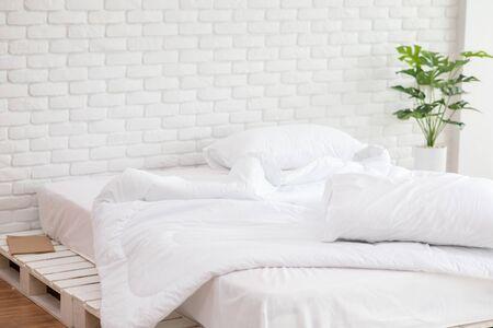 Lit en désordre avec oreiller blanc et couverture avec lumière naturelle le matin, lit en désordre après le réveil, concept de lit en désordre Banque d'images