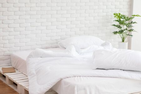 Messed bed with white pillow and blanket with natural light in the morning,Messy bed after wake up,Messy bed Concept Stockfoto