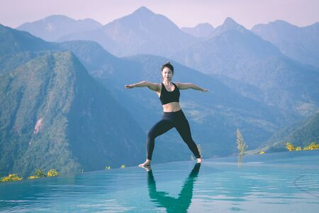 Beautiful Attractive Asian woman practice yoga warrior or Virabhadrasana Pose on the pool above the Mountain peak in the morning in front of beautiful nature views in SAPA vietnam,Feel so comfortable 스톡 콘텐츠