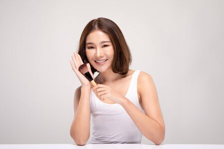 Beautiful Asian young woman smile and holding make up brush with healthy Clean and Fresh skin feeling so happiness and cheerful,Isolated on white background,Beauty Cosmetics Concept