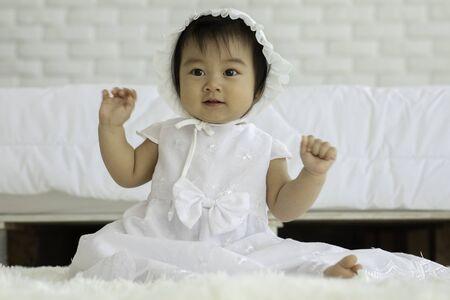 Leuke lieve schattige Aziatische baby met witte jurk zittend op tapijt glimlachend en spelend met geluk emotioneel in een gezellige slaapkamer, Healthy Baby Concept