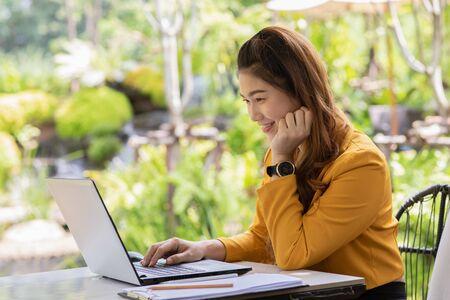 Mujer joven asiática de negocios trabajando con computadora portátil y pensando en obtener ideas y requisitos en el inicio de negocios sintiéndose tan feliz, concepto de inicio de pequeñas empresas