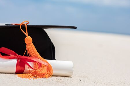 Close up Graduation cap and certificated on the beach with beautiful sea in summer,Education in summer Concept