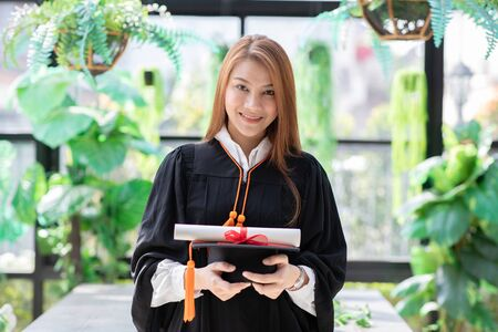Beautiful Attractive Asian graduation woman in gown holding graduation cap and certificated so proud and happiness for finish graduate,Education Success Concept Stock Photo