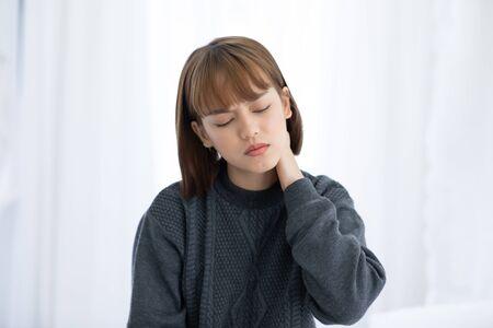 jonge Aziatische vrouw die op bed zit, heeft nekpijn na het wakker worden in de ochtend, Gezondheidszorgconcept