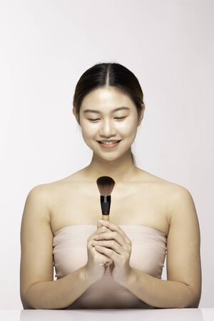 Beautiful Asian young woman smile and holding make up brush with healthy Clean and Fresh skin feeling so happiness and cheerful,Isolated on white background,Beauty Concept