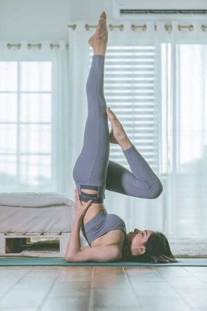 Attractive Asian woman practice yoga Shoulder stand pose to meditation in bedroom after wake up in the morning Feeling so comfortable and relax,Healthcare Concept