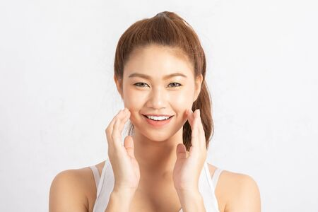Piękny, atrakcyjny, uroczy, azjatycki uśmiech młodej kobiety z białymi zębami i dotykając miękkiego policzka uczucie tak szczęścia i wesołości ze zdrową skórą, na białym tle, koncepcja urody Zdjęcie Seryjne