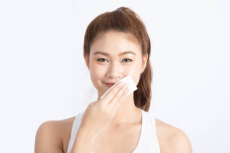 Attractive Charming Asian young woman smile and using tissue with toner for cleaning makeup feeling so fresh and clean with healthy skin, isolated on white background, Beauty Cosmetics Concept Zdjęcie Seryjne