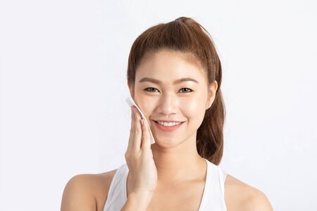 Attractive Charming Asian young woman smile and using tissue with toner for cleaning make up feeling so fresh and clean with healthy skin,isolated on white background,Beauty Cosmetics Concept Standard-Bild