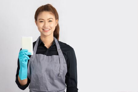 Beautiful Attractive Asian Maid smile and holding sponge for cleaning feeling so happiness and confident, Isolated on grey background, Maid Cleaning Service Concept