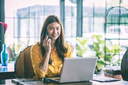 Beautiful Attractive Asian woman working with laptop smile and talking with customer in smartphone to get idea and requirement for success job outside office in coffee shop,Business Startup Concept Standard-Bild