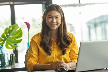 Beautiful Attractive Business Asian woman working with laptop and looking in monitor smile and have positive emotional feeling so happiness,Business Startup Concept