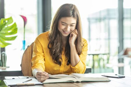 Beautiful Attractive Asian woman reading book for learn and education smile and positive thinking feeling so happiness and comfortable,Education Concept