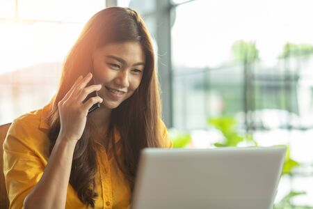 Beautiful Attractive Asian woman working with laptop smile and talking with customer in smartphone to get idea and requirement for success job outside office in coffee shop,Business Startup Concept Foto de archivo