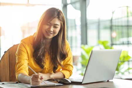 Beautiful Attractive Asian woman working with laptop smile and writing idea and requirement for success job outside office in coffee shop,Business Concept,Warm Tone
