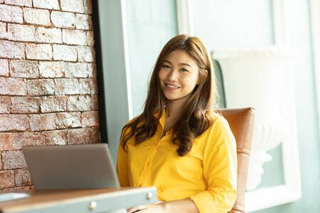 Beautiful Attractive Business Asian woman working with laptop and looking in monitor smile and have positive emotional feeling so happiness,Business Startup Concept,Warm Tone