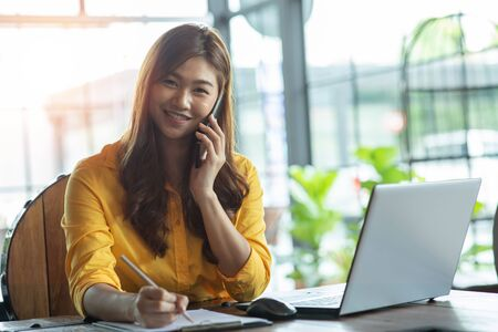 Beautiful Attractive Asian Business woman writing down requirement to book and talking with customer in smartphone,Feeling so happiness and working with service mind,Business and Finance Concept Foto de archivo